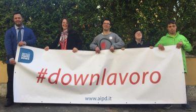 """Striscione con la scritta """"#downlavoro"""" tenuto da persone con la sindrome di Down"""
