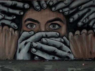 Un'opera di street art realizzata a Berlino raffigura il volto di una persona circondata da tante mani, due delle quali sono posizionate sulla bocca impedendole di parlare