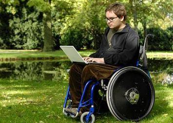 Uomo in sedia a rotelle mentre lavora al PC
