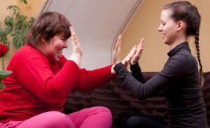 Due donne, una delle quali con disabilità intellettiva, giocano assieme ciascuna battendo le proprie mani contro quelle dell'altra (foto dell'ANFFAS di Massa Carrara)