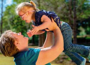 In un parco una madre gioca con la sua bambina di due o tre anni, e con sindrome di Down, sollevandola in aria con le braccia