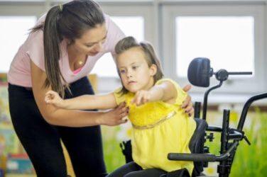Caregiver familiare insieme alla sua bimba con grave disabilità