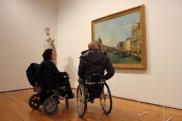 Persone con disabilità motoria in carrozzina in visita a un museo