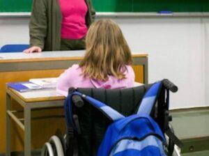 Una giovane alunna in sedia a rotelle ritratta di spalle al suo banco all'interno della classe.