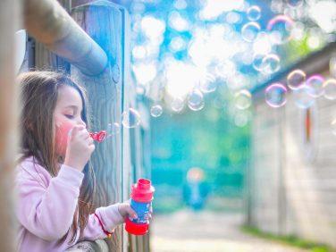 Bambina che soffia bolle di sapone