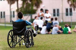 Bimbo in carrozzina nel giardino di scuola che guarda i compagni